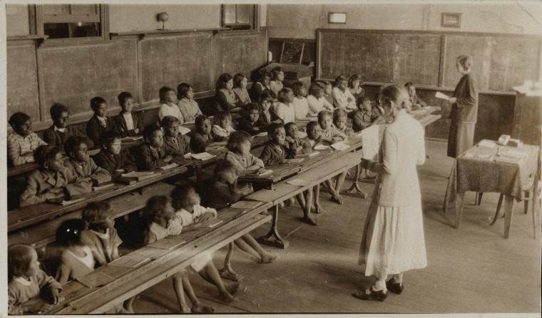 BA1340/ERA3/20B: Doreen Murray opens school in prayer at Mt Margaret Mission school with Dorothy Kristiansen (foreground) and M.M. Bennett, 1934 (Click to Start Zoom)